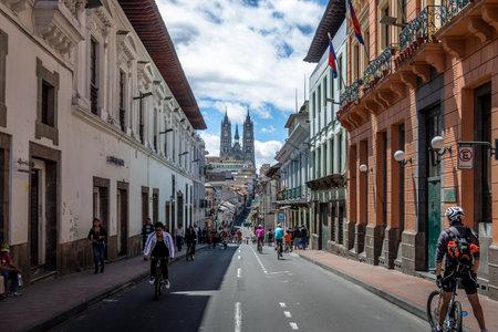 Bikers and pedestrians on a sunday closed street of Quito and Basilica del Voto Nacional - Quito, Ecuador