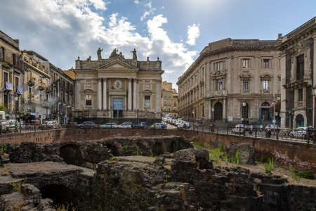 archaeological: Ruins of the Roman Amphitheater at the Stesicoro Square with San Biagio Church on background - Catania, Sicily, Italy Editorial