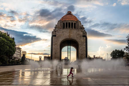 Girl playing with the water fountain in front of Monument to the Mexican Revolution (Monument to the Revolution) - Mexico City, Mexico 版權商用圖片 - 80457095
