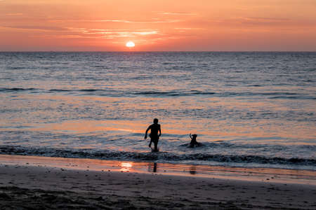 Man and dog silhouette at Beautiful sunset in Mancora Beach - Mancora, Peru Stock Photo
