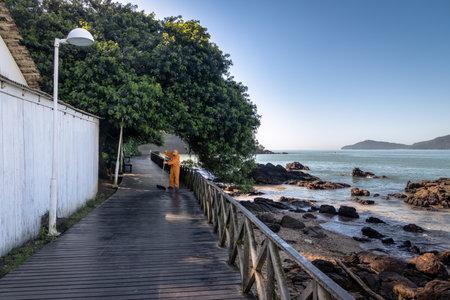 Janitor sweeping a wooden walkay - Balneario Camboriu, Santa Catarina, Brazil