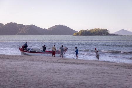 Fishermen at Beach with Island of Cabras Island on background - Balneario Camboriu, Santa Catarina, Brazil Editorial