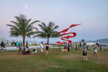People having fun at sunset in the garden at Marine Outfall - Santos, Sao Paulo, Brazil