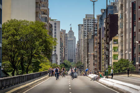 People enjoying the weekend at elevated highway known as the Minhocao (High President Joao Goulart) with old Banespa (Altino Arantes) on background - Sao Paulo, Brazil