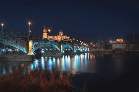 Salamanca Skyline view with Cathedral and Enrique Estevan Bridge from Tormes River at night - Salamanca, Castile and Leon, Spain Stock fotó