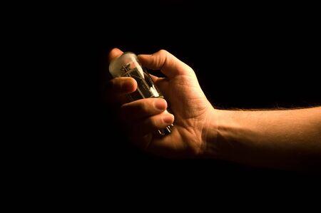 distortion: Hand holding a broken vacuum tube on black background
