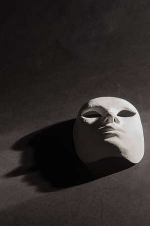 White neutral mask spotlight shadow on black background with scratches photo