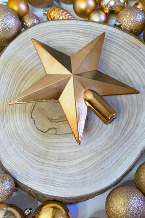 Christmas star on wooden log and golden holiday decorations