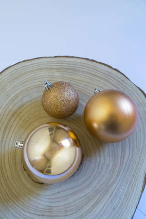 Golden Christmas balls on wooden log and white background Archivio Fotografico