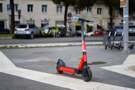 Rental electric scooter parked on the side walk on a rainy day