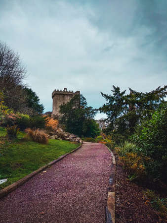 Old castle on top of a hill surrounded by gardens and trees on a cloudy day
