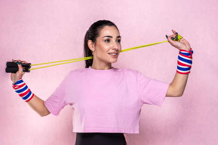 Beautiful young caucasian sportswoman posing in pink colored sport tshirt outfit with black body and black and white socks - Pretty sporty brunette athletic model girl posing with jumping rope during sport training