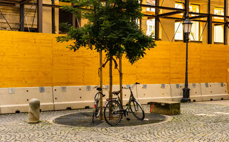 Beautiful pair of parked bicycles near the tree at the center of Munich, Germany