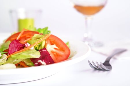 Healthy vegetable salad next to fork and glass of wine Stock fotó