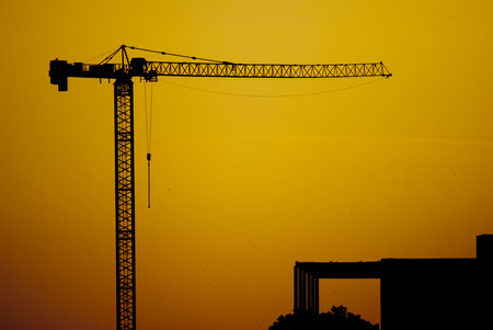Construction crane silhouette on the sunset sky background