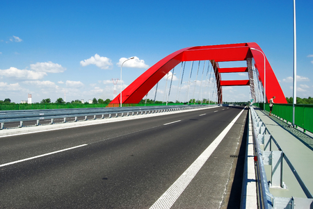 Modern red bridge on the dual carriage road in Poland Reklamní fotografie - 90428024