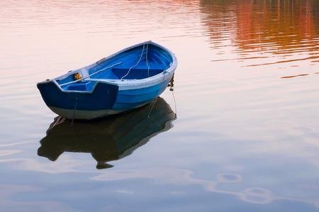 LIttle boat adrift on the water while sunset. Stock fotó