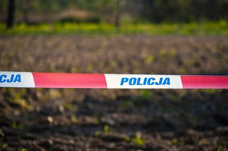 """Red and white protection tape with """"POLICJA"""" inscription. Polish police """"do not cross"""" tape"""