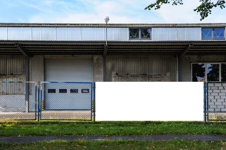 Blank white advertising banner mounted on the fence of warehouse with loading ramp