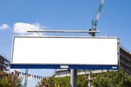 Huge blank white advertising billboard in front of apartment building under construction