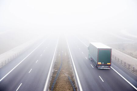 Lorry rides fast on a highway in a misty cold day. Concept of road safety problem.