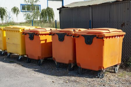Row of orange and yellow garbage bins for sorted waste Standard-Bild