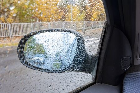 Riding car viewed in the car mirror covered with rain drops Imagens