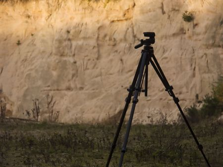 Tripod in front of a sandstone wall with warm sunset light falling on it