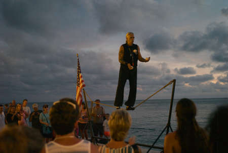 KEY WEST, FLORIDA - July 12 2012: Man on a tightrope at dusk in Key West, Florida.