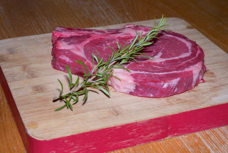 Fresh, Red, Juicy, Raw Prime Rib of Beef on a Wooden Board with Rosemary