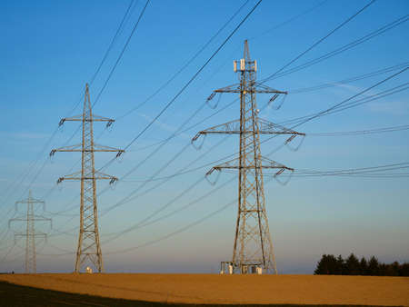 A High Voltage Power Pylons Against a Bright Blue Sky in the Countryside