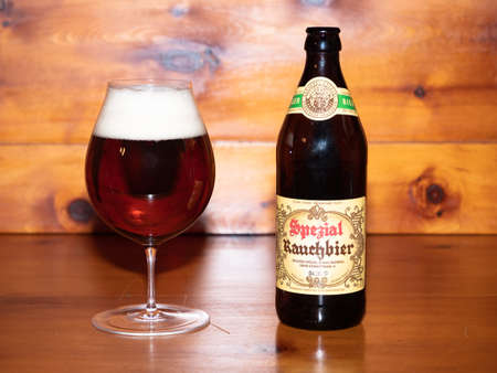 Bamberg, Germany - March 1 2019: Dark Bamberg Smoked Beer from the famous Spezial Brewery in Bamberg, Bavaria, Germany in the Glass with its Bottle on a wood table. Stok Fotoğraf - 124912282