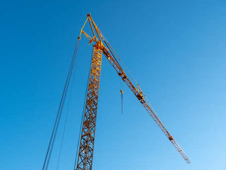Large, Yellow Construction Crane against a Bright Blue Sky