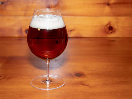Refreshing, Amber Ale or Beer in a Tulip Shaped Glass on a Wood Background Stok Fotoğraf - 124959011