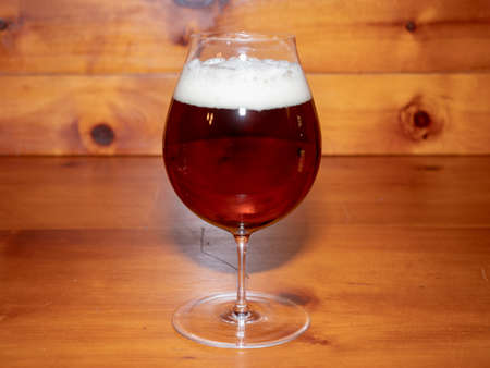 Refreshing, Amber Ale or Beer in a Tulip Shaped Glass on a Wood Background Stok Fotoğraf - 124959015