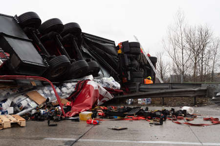 Enns, Upper Austria, Austria - March 15 2019: Large truck flipped over in a heavy traffic accident on the A1 Motorway called Westautobahn in German near Enns in Upper Austria. The truck is upside down  after the crash and the cargo has been scattered on t