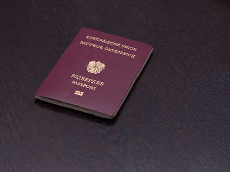 Red European Passport of Austrian Nationality on a Wooden Table 免版税图像
