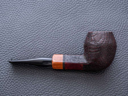 An Old Fashioned Dark Brown Rusticated Army or Bulldog Smoking Pipe on a Black Leather Background - A Concept for Smoking Stock Photo