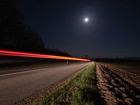 Country Road at Night Illuminated by a Passing Car  with Full Moon and Red Light Trails - Long Exposure