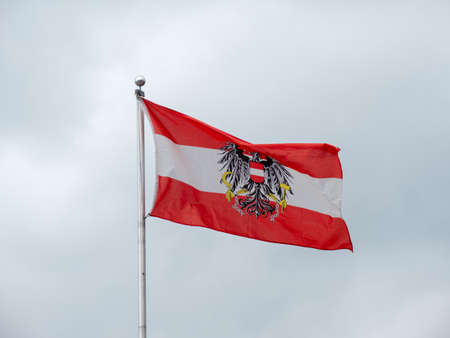 Austrian Flag with the Federal Eagle Coat of Arms and Red, White and Red Colors flying on a Grey Background