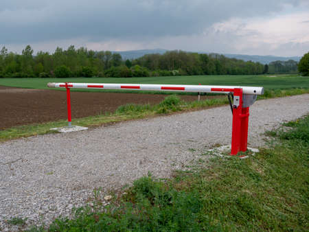 Closed Red and White Boom Gate or Boom Barrier on a Gravel Path in the Countryside Stock Photo