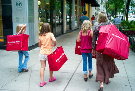 Chicago, Illinois, USA - July 25 2009: A woman and three girls returning from shopping with large red bags from American Girl Place in Chicago, Illinois. A concept for shopping and consumerism.