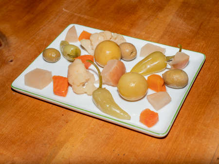 Assorted Spicy Turkish Pickles - Called Tursu - Lemon, Pepper, Olives, Carrots on a White Rectangular Plate on a Wood Table Imagens