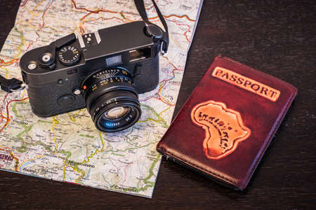 Travel Photography Concept - Photo Camera, Passport and Map on a Dark Wood Background - Vintage Look