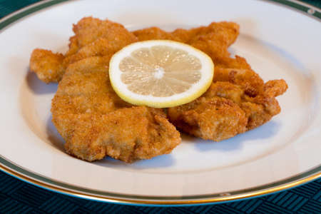 Tasty Viennese Schnitzel or Wiener Schnitzel on an Elegant Plate with Lemon, Traditional Austrian Dish