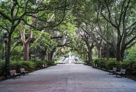 Fontanna w parku Forsytha z dużymi drzewami i ławkami parkowymi w Savannah, Georgia, Stany Zjednoczone