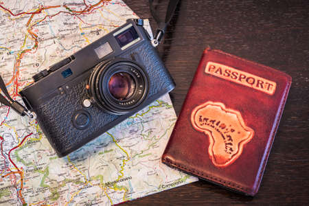 Travel Photography Concept - Black, Retro, Vintage Photo Camera, Passport and Map on a Dark Wood Background - Vintage Look
