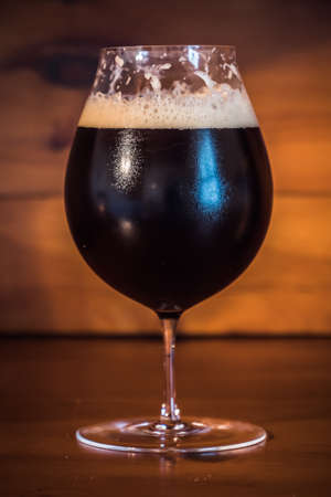 Dark Beer or Ale like Bamberg Smokebeer in a Tulip Glass on a Wood Background Archivio Fotografico