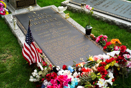 Memphis, Tennessee, United States - July 21 2009: The Grave of Elvis Presley in Graceland decorated with Flowers and a Flag.