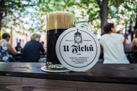 Prague, Czech Republic - July 10 2020: Glass with Dark Beer in U Fleku Beer Garden with Coaster and Logo on a Table. Redactioneel